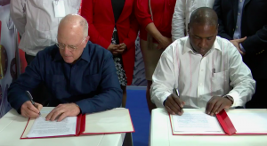 One year in the making:  John Deere & Co. Vice President Charles Stamp, l., and Maquimport General Director Aner Pérez sign the agreement at the Havana International Fair. Still photo: ABC 10 Miami